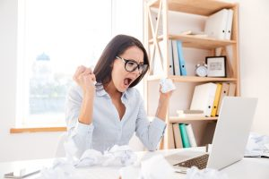 Picture of angry businesswoman sitting in her office and screaming while tear paper.