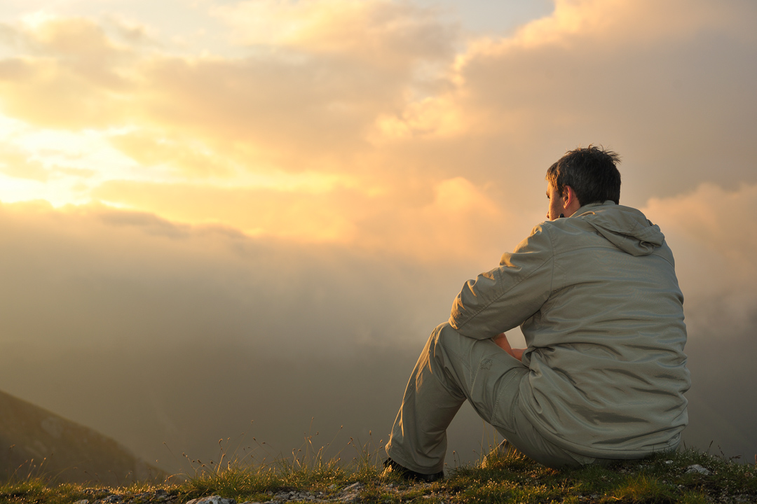 Man sitting at Mountain Top seeing Sunrise