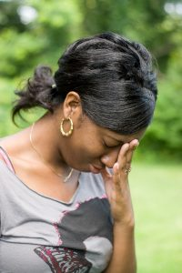 A young woman holds her hand on her forehead in anguish over stress she is experiencing.