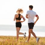 Back view of young fitness man and woman doing jogging sport outdoors